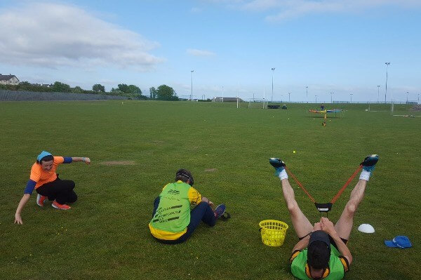 Staff members participating in a group activity on a grass pitch as part of team building excercise.