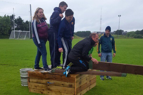A team attempts to cross a river using a plank of wood and teamwork.