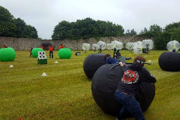 Wide shot of participants playing archery game with masks on.