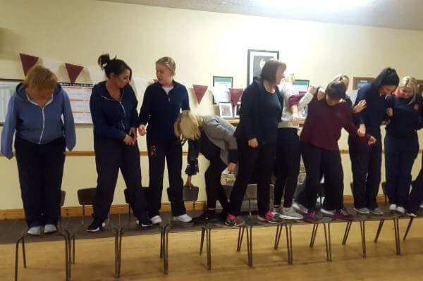 Staff members on chairs participating in a team building excercise.